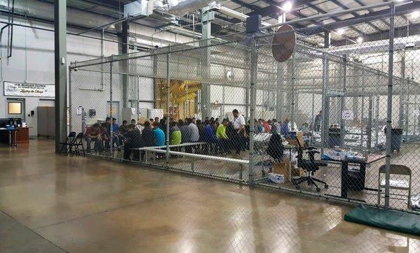 Personas que han sido detenidas por intentar entrar a EEUU sin autorización están sentadas en una de las jaulas en el centro de McAllen, Texas (U.S. Customs and Border Protection's Rio Grande Valley Sector vía AP)