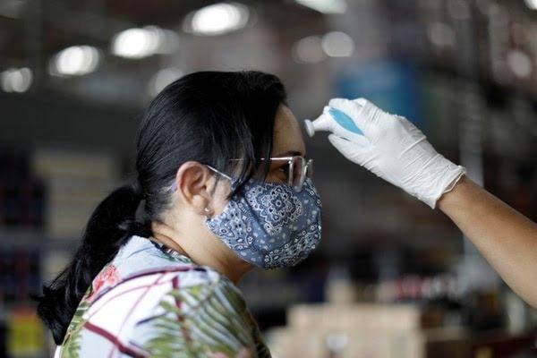 Empleados de supermercados controlan la temperatura de personas que ingresan durante el brote de coronavirus en Brasilia, Brasil, 20 de marzo del 2020. REUTERS/Ueslei Marcelino