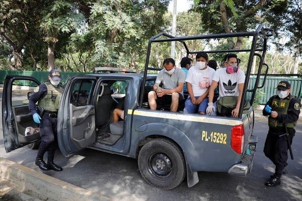 Policías y militares detienen personas en un puesto de control por la cuarentena contra el coronavirus en Lima, Perú, 26 de marzo de 2020. REUTERS/Sebastian Castaneda.